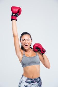 Portrait d'une femme de remise en forme de succès avec des gants de boxe célébrant sa victoire isolée sur un backgorund blanc