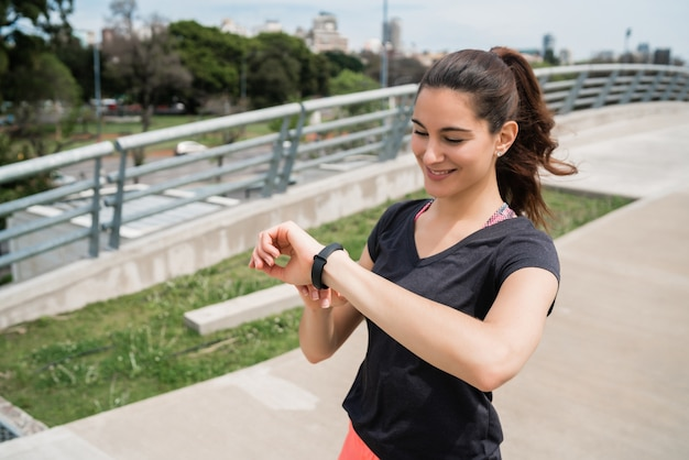 Portrait d'une femme de remise en forme vérifiant l'heure sur sa montre intelligente. concept de sport et de mode de vie sain.