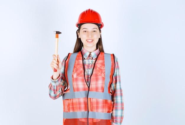 Portrait de femme réparatrice en uniforme debout avec un marteau sur un mur blanc.