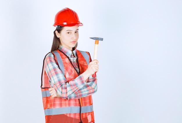 Portrait de femme réparatrice en uniforme tenant un marteau sur un mur blanc.