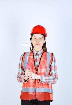 Portrait de femme réparatrice en uniforme tenant un rouleau de peinture sur un mur blanc.