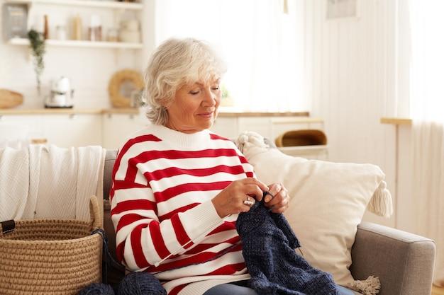 Portrait de femme retraité aux cheveux gris concentré dans des vêtements décontractés qui passe le temps à tricoter pull assis contre une chambre intérieure confortable