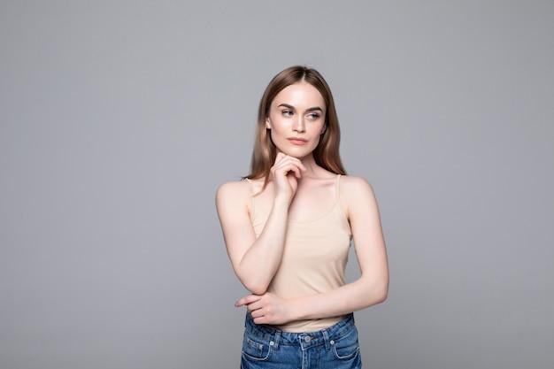 Portrait de femme réussie regardant de côté et tenant le doigt sur la joue tout en souriant isolé sur mur gris