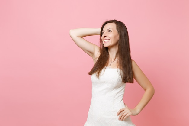 Portrait d'une femme rêveuse joyeuse en élégante robe blanche debout et gardant la main près de la tête