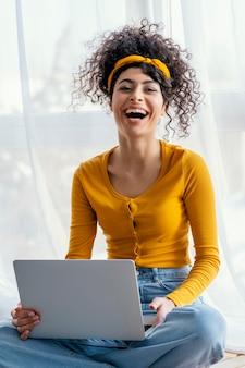Portrait de femme en riant à l'aide d'un ordinateur portable