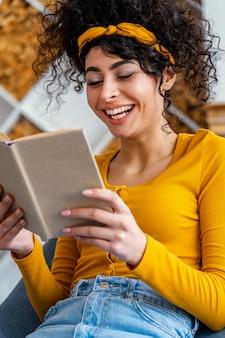 Portrait de femme en riant en lisant un livre