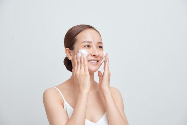 Portrait d'une femme riante joyeuse appliquant de la mousse pour se laver le visage.