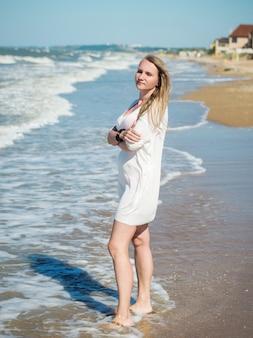 Portrait d'une femme en robe blanche aveuglée par le soleil face à la mer.
