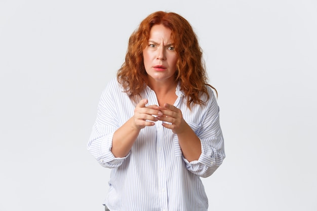 Portrait de femme rousse d'âge moyen confus regardant avec incrédulité, ne peut pas comprendre quelque chose, fronçant les sourcils et regardant perplexe, pointant le doigt hésitant, debout mur blanc.