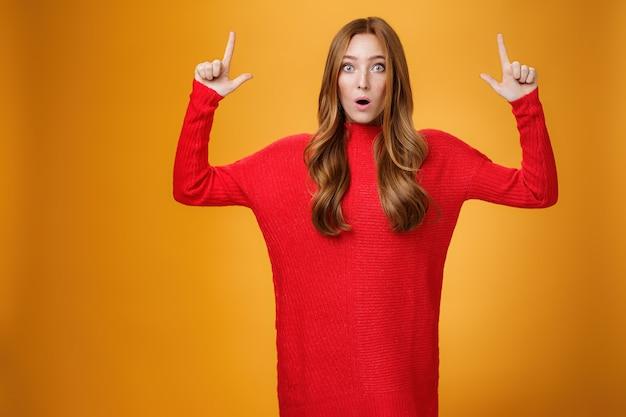 Portrait d'une femme rousse attrayante et élégante de 25 ans en robe rouge tricotée haletant d'étonnement bouche ouverte interrogée et surprise en pointant vers une promotion étonnante sur un mur orange