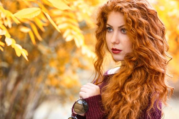 Portrait de femme rousse aux feuilles jaunes