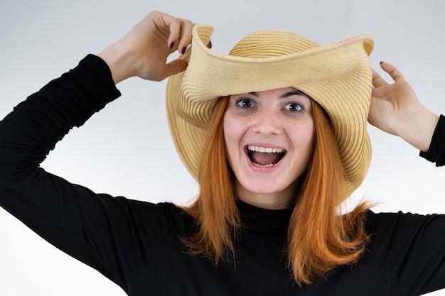 Portrait de femme rousse drôle en chapeau de paille jaune sac.