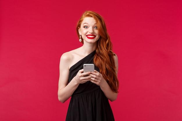 Portrait de femme rousse excitée et amusée, vêtue d'une robe noire à sa date ou nuit de bal, tenant un téléphone mobile, souriant rayonnant, debout sur un mur rouge optimiste