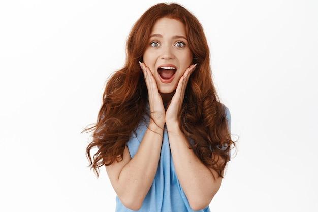 Portrait de femme rousse impressionnée et excitée sur blanc