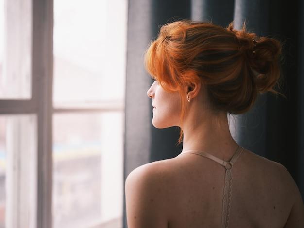 Portrait d'une femme rousse près de la fenêtre
