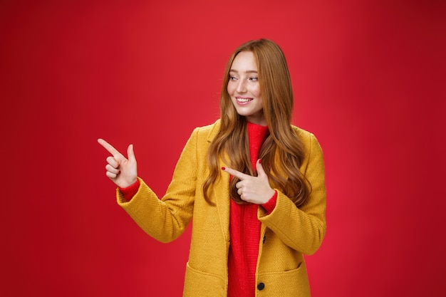 Portrait d'une femme rousse séduisante curieuse et heureuse en manteau jaune pointant vers la gauche avec un sourire intrigué ravi observant un espace de copie impressionnant sur fond rouge.