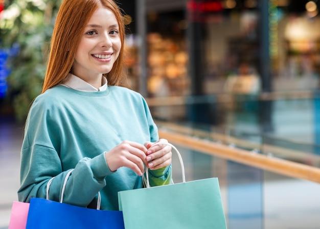 Portrait de femme rousse tenant des sacs à provisions