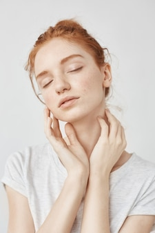 Portrait d'une femme rousse tendre avec des taches de rousseur et les yeux fermés.