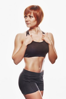 Portrait de femme rousse en tenue de sport. studio tourné, isolé, fond blanc