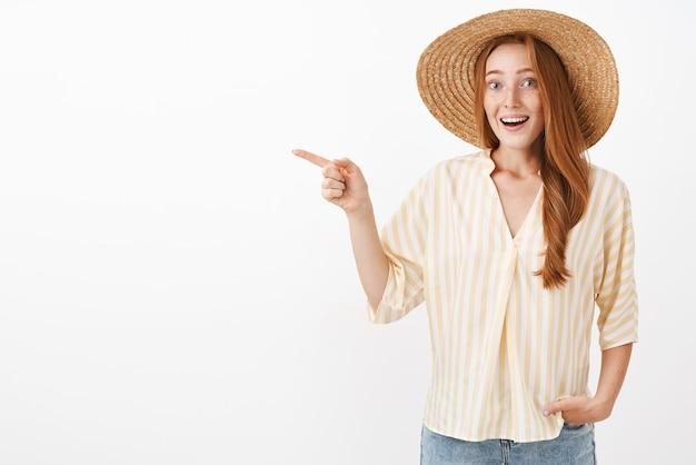 Portrait de femme rousse timide féminine impressionnée et excitée avec des taches de rousseur en chapeau de paille et chemisier d'été rayé pointant vers la gauche avec étonnement souriant largement de frisson