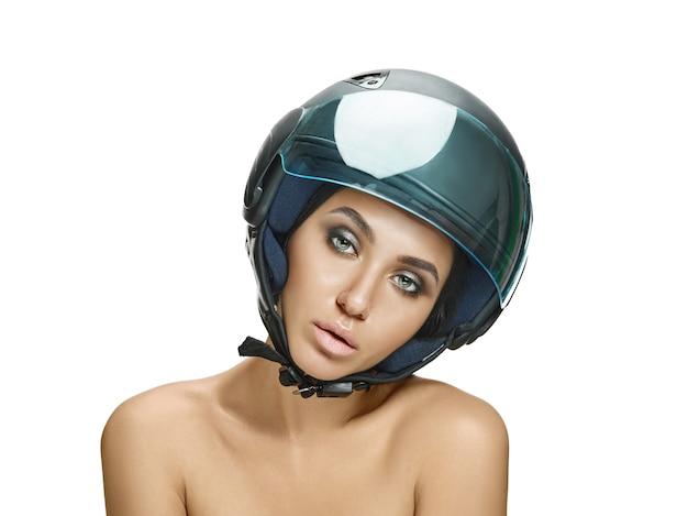 Portrait de femme séduisante en casque de moto sur mur blanc studio