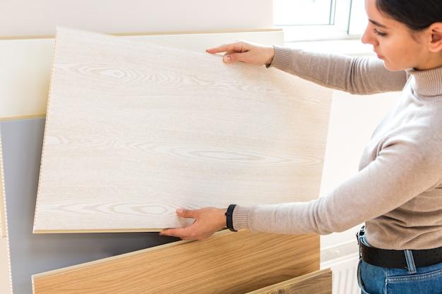 Portrait de femme séduisante dans le magasin de construction en choisissant une surface en bois stratifié pour la rénovation domiciliaire et de nouvelles idées de design.