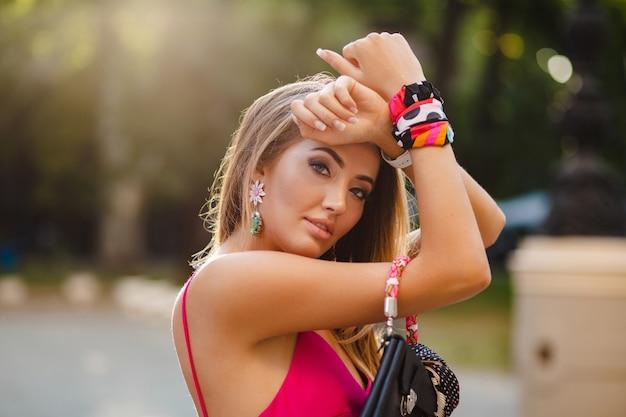 Portrait de femme séduisante élégante sexy en robe d'été sexy rose marchant dans la rue