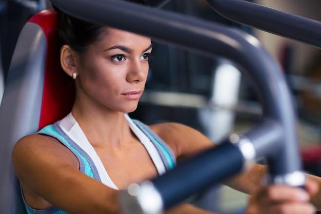 Portrait de femme séduisante d'entraînement sur la machine d'exercices à la salle de fitness