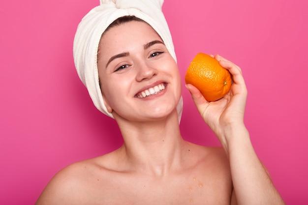 Portrait de femme séduisante à moitié nue souriante, dame détient des tranches d'orange sur son visage et regarde la caméra isolée sur rose. jolie femme avec une serviette sur la tête prend soin de la peau dans la salle de bain.