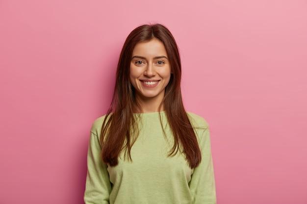 Portrait de femme séduisante a la peau saine, a le sourire à pleines dents, regarde directement, porte un pull vert, a de longs cheveux raides, pose contre un mur rose pastel. concept d'expressions de visage