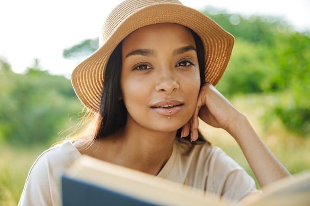 Portrait d'une femme séduisante portant un piercing à la lèvre et un chapeau de paille lisant un livre assis sur l'herbe dans un parc verdoyant