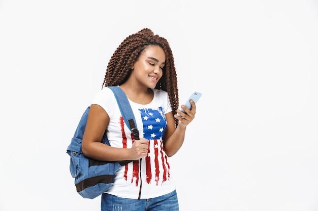 Portrait d'une femme séduisante portant un sac à dos souriant et tenant un téléphone portable tout en se tenant isolé contre un mur blanc