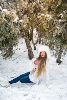 Portrait de femme séduisante avec promenade de café sur le parc d'hiver