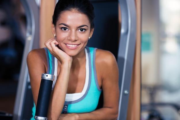 Portrait d'une femme séduisante souriante debout dans une salle de fitness