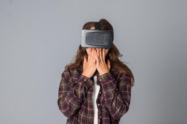 Portrait de femme séduisante testant des lunettes de réalité virtuelle en studio sur mur gris