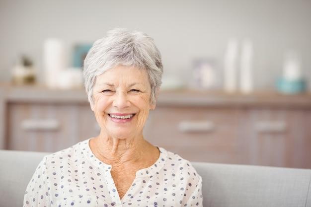 Portrait de femme senior assise sur un canapé