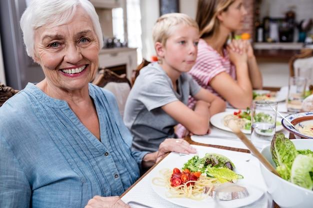 Portrait de femme senior ayant un repas avec sa famille