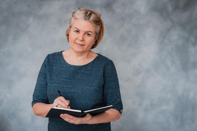 Portrait d'une femme senior belle entreprise sur un mur gris
