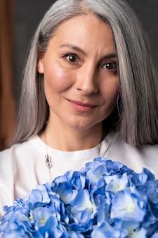 Portrait de femme senior avec bouquet de fleurs