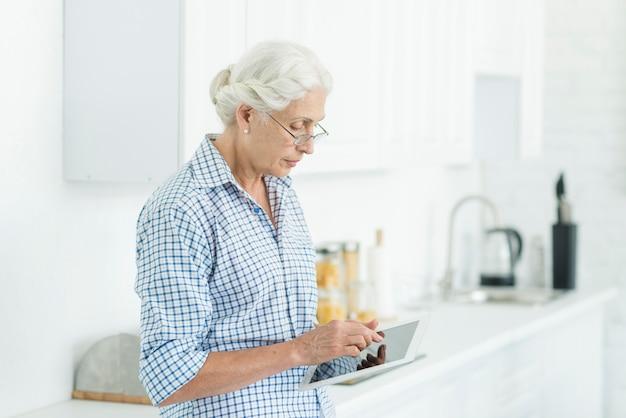 Portrait de femme senior debout dans la cuisine en utilisant une tablette numérique