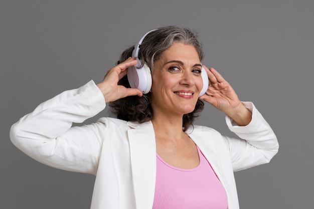 Portrait de femme senior élégante avec une paire d'écouteurs