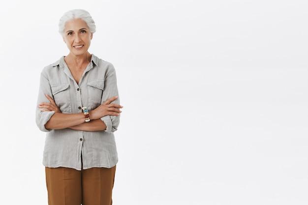 Portrait de femme senior européenne charmante et charismatique confiante en tenue décontractée, croisant les bras sur le corps souriant avec regard assuré