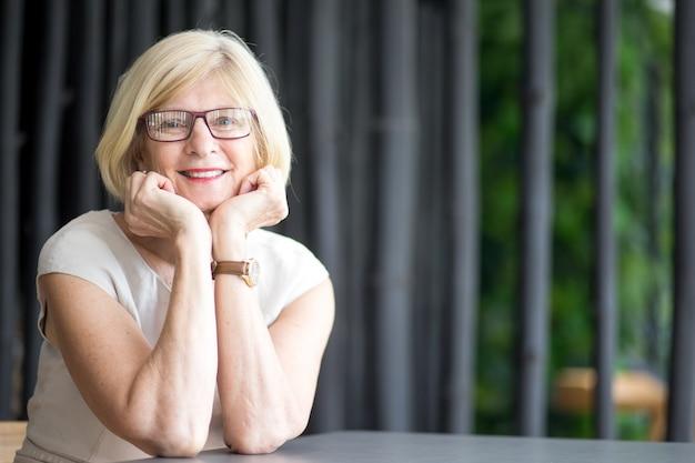 Portrait d'une femme senior heureuse allongée sur les bras