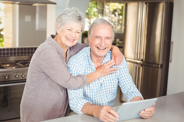 Portrait de femme senior heureuse embrassant homme avec tablette