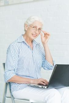 Portrait de femme senior heureuse avec ordinateur portable