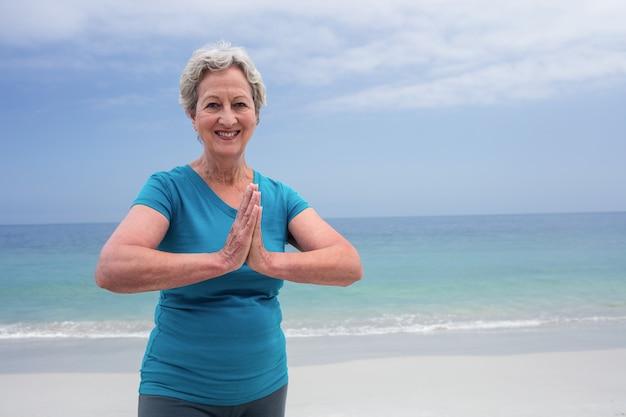 Portrait de femme senior heureuse en position du lotus