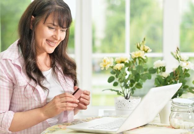 Portrait de femme senior avec ordinateur portable à la maison