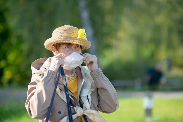 Portrait de femme senior positive portant un masque facial en raison d'un coronavirus - mode de vie des personnes âgées retraitées en vacances d'été