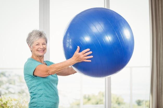 Portrait de femme senior souriante tenant un ballon d'exercice
