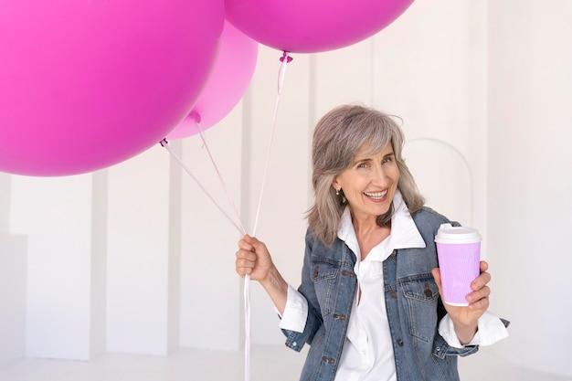 Portrait de femme senior souriante tenant une tasse et des ballons roses